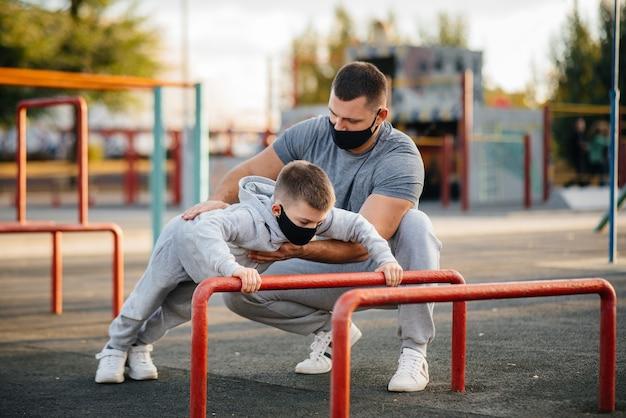 아버지와 아들은 일몰 동안 마스크에 스포츠 분야에서 스포츠를 재생