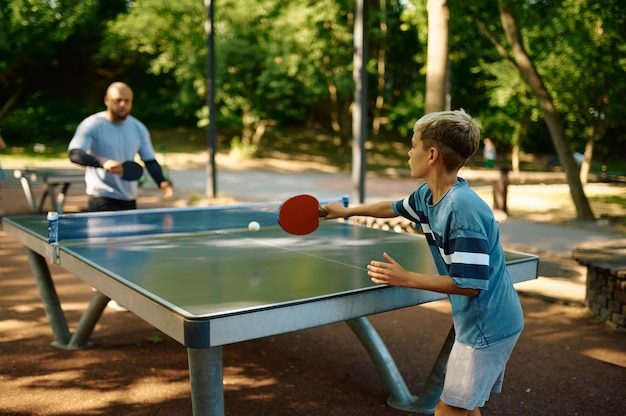 父と息子は屋外で卓球をします。家族は健康的なライフスタイルをリードし、パパと男の子、サマーパークで卓球トレーニングをします