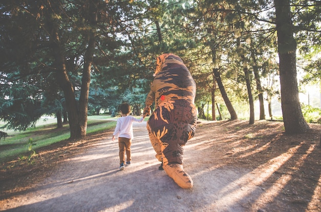 아버지와 아들은 공룡 의상과 함께 공원에서 놀고 가족과 함께 재미 있습니다.