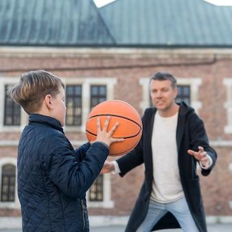 Отец и сын играют в баскетбол на улице