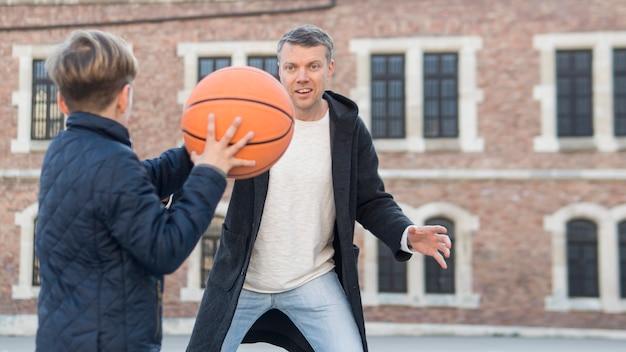 Отец и сын играют в баскетбол через плечо