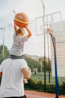 Отец и сын играют в баскетбол
