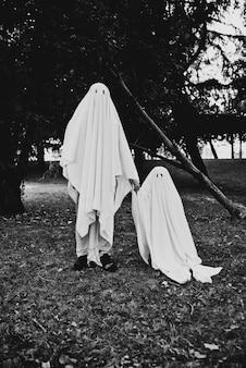 Отец и сын играют призраков с белыми простынями в саду, концептуальные фотографии о праздниках хэллоуина
