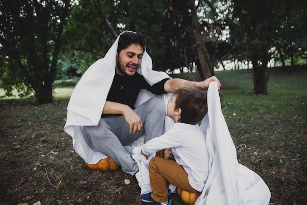 Отец и сын играют призраков с белыми простынями в саду, концептуальные фотографии о хэллоуине