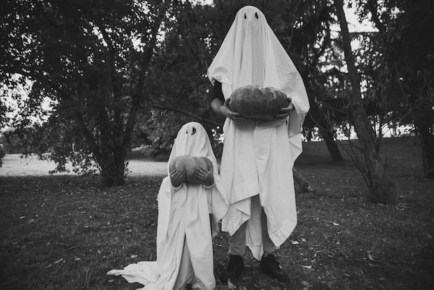 Отец и сын играют призраков с белыми простынями в саду