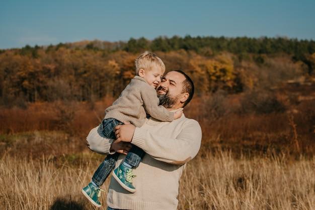 Отец и сын играют, веселятся на природе