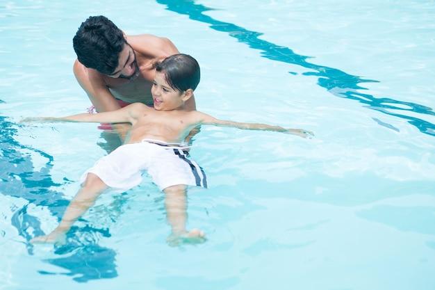 Отец и сын, играя в бассейне