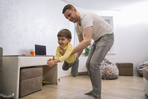 Отец и сын играют в гостиной