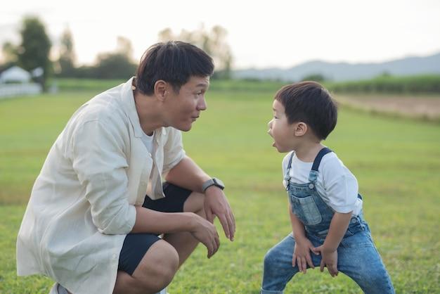 夕暮れ時に公園で遊ぶ父子。フィールドで楽しむ人々。フレンドリーな家族と夏休みのコンセプト。父と息子の足が公園の芝生の上を歩く