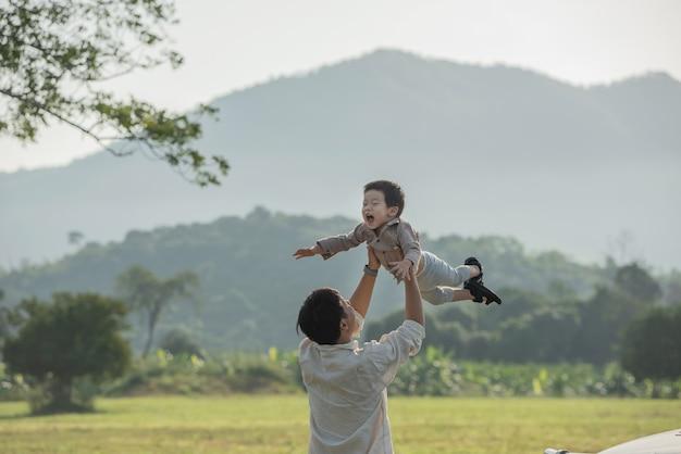 아버지와 아들이 일몰 시간에 공원에서 연주. 사람들은 현장에서 재미. 친절한 가족과 여름 휴가의 개념.