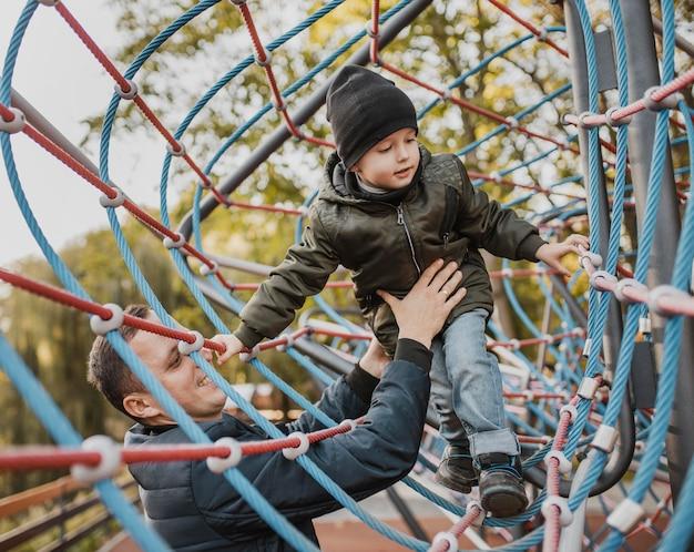 Отец и сын играют в парке