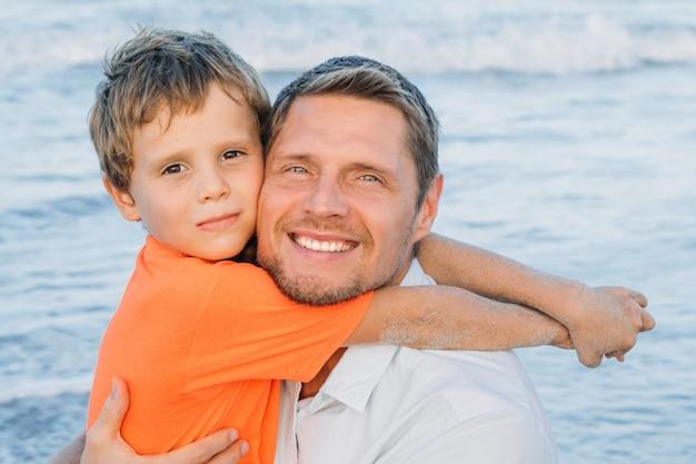 一緒にビーチで遊んでいる父と息子。明るく幸せな家族の肖像画。フレンドリーな家族のコンセプト。