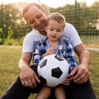 Отец и сын играют на футбольном поле