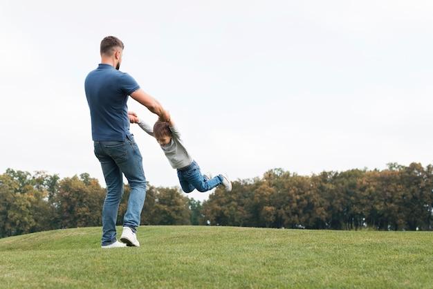 Отец и сын играют на траве