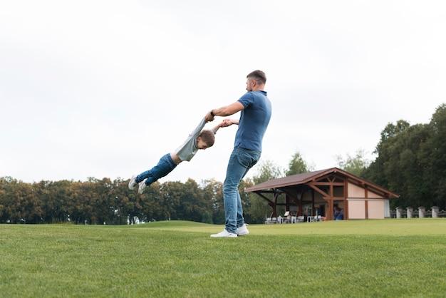 Отец и сын, играя на открытом воздухе