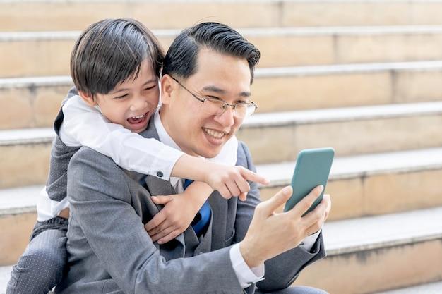 都市のビジネス地区で一緒にスマートフォンをプレイする父と息子