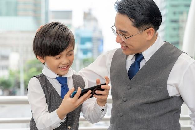 Отец и сын вместе играют в смартфон в деловом районе города