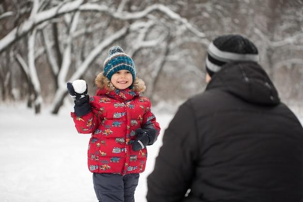 Отец и сын играют в снежки в зимнем парке