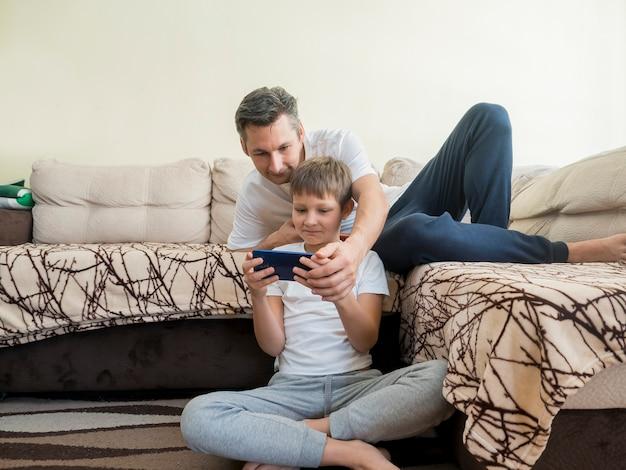 Отец и сын играют в видеоигры на мобильном телефоне