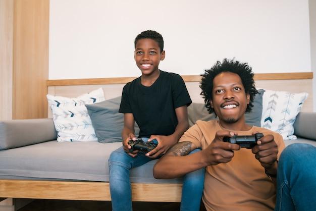 Отец и сын вместе играют в видеоигры дома.