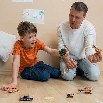 Отец и сын играют с игрушками на полу