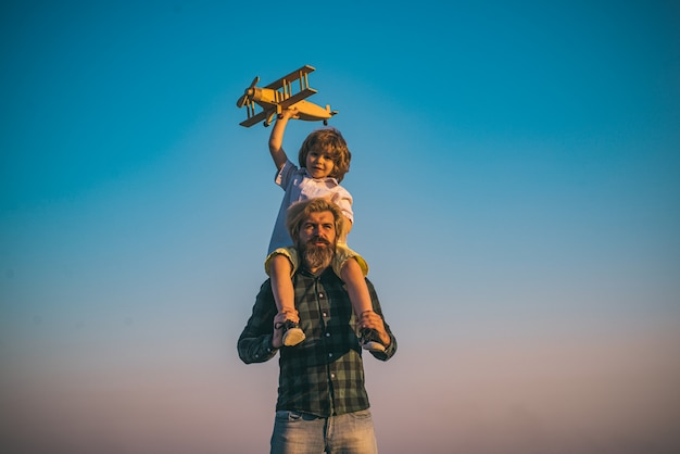 木製の飛行機で遊んでいる父と息子。息子を肩に乗せた父。