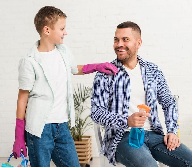 父と息子のクリーニング製品を押しながらポーズ