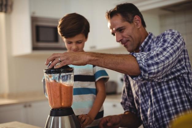 Отец и сын готовят коктейль на кухне