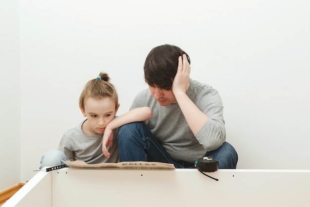 아버지와 아들이 새 집에 가구를 조립하라는 지침을 읽고 있습니다. 가구 조립을 직접하십시오. 아버지가 집에서 가구를 조립하는 것을 돕는 아들.