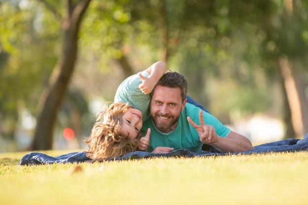 公園で自然にリラックスした父と息子幸せな父と子は公園で休暇で夏の時間を楽しんでいます