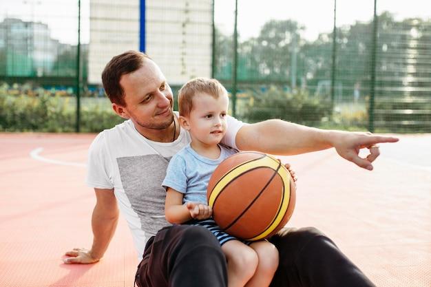 バスケットボールのフィールドでリラックスした父と息子