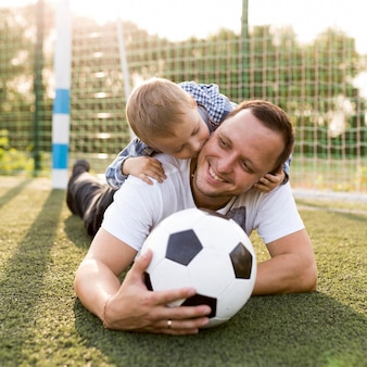 サッカー場で休んでいる父と息子