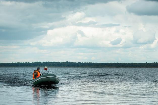 父と息子は湖でモーターボートに乗ります。