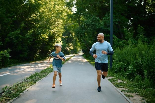 屋外の散歩道を走っている父と息子。家族は夏の公園で健康的なライフスタイル、フィットネストレーニングをリードしています