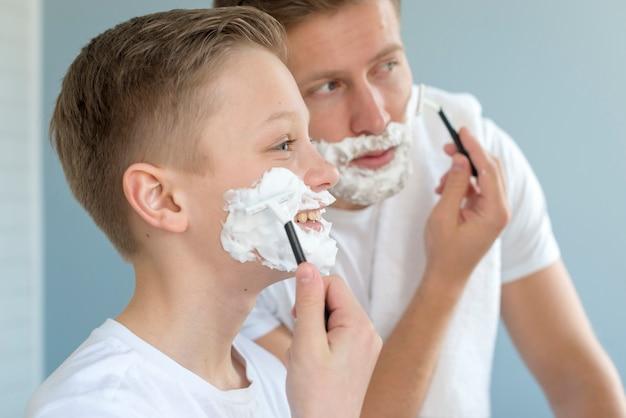 Отец и сын бреются в ванной комнате, вид сбоку