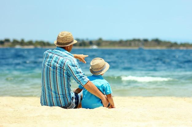 父と息子は海のそばに座って夢を見る
