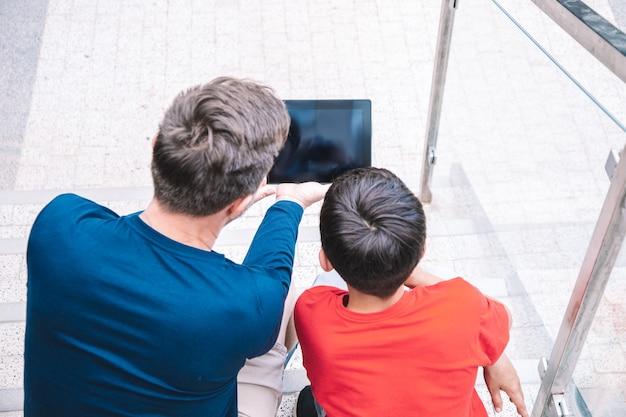 Отец и сын сидят на ступенях городского здания и вместе смотрят планшет. понятие о технологиях. современный образ жизни. фото высокого качества