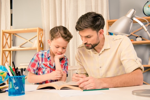 Отец и сын сидят с интересной книгой и обучением