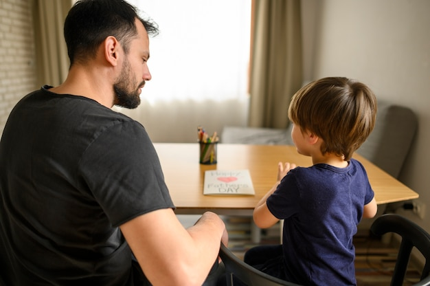 父と息子が一緒にテーブルに座って