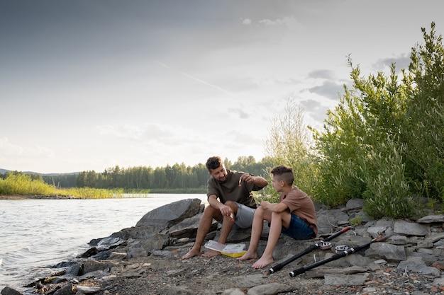 낚시하는 동안 호수 앞에 앉아 아버지와 아들