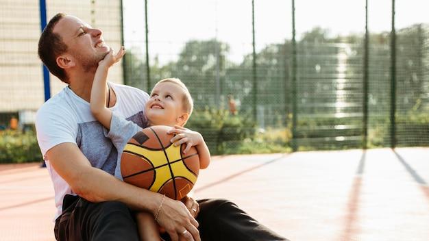 아버지와 아들이 농구장에 앉아