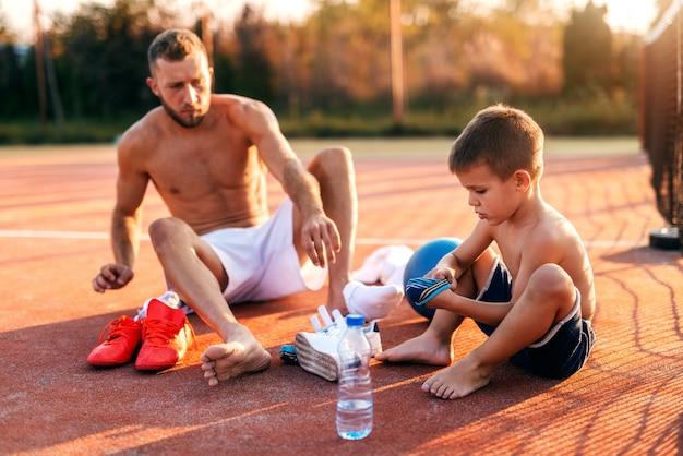아버지와 아들이 법원에 앉아서 훈련을 위해 드레싱. 아침에 여름.
