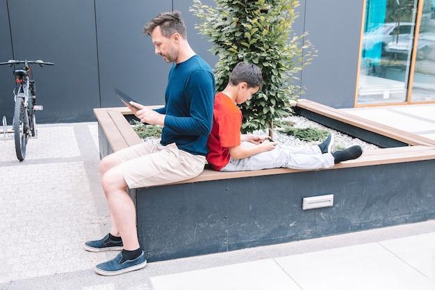 Отец и сын проводят время в городском парке, сидя спиной к спине и используя смартфон или планшет. современные технологии. современный образ жизни
