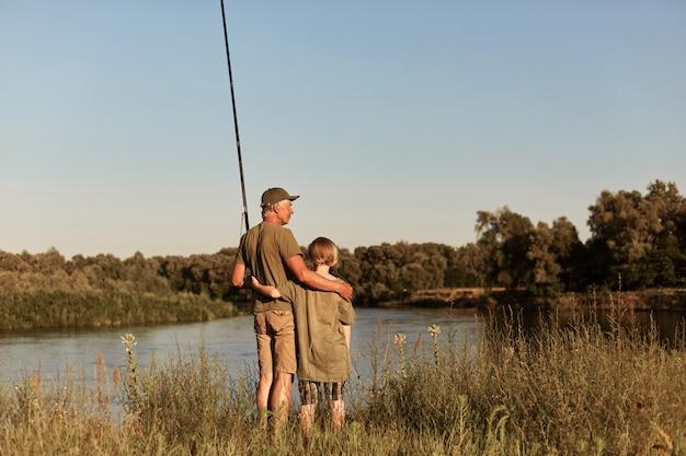 父と息子は釣り竿の近くの川に抱き合って立ち、カジュアルな服装で美しい夕日を楽しみ、湖の近くで夏の日を過ごします。
