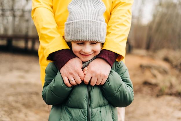 Отец и сын стоят на берегу озера и держатся за руки счастливая семья с ребенком, мальчик играет