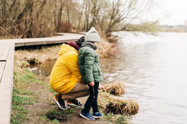 Отец и сын стоят на берегу озера и играют с водой счастливая семья с маленьким мальчиком