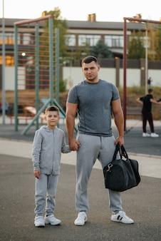 아버지와 아들은 일몰 동안 훈련 후 스포츠 필드에 서