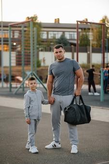 Отец и сын стоят на спортивном поле после тренировки во время заката.