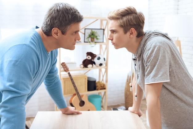 Отец и сын, стоя лицом к лицу.