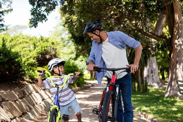 아버지와 아들이 공원에서 자전거와 함께 서